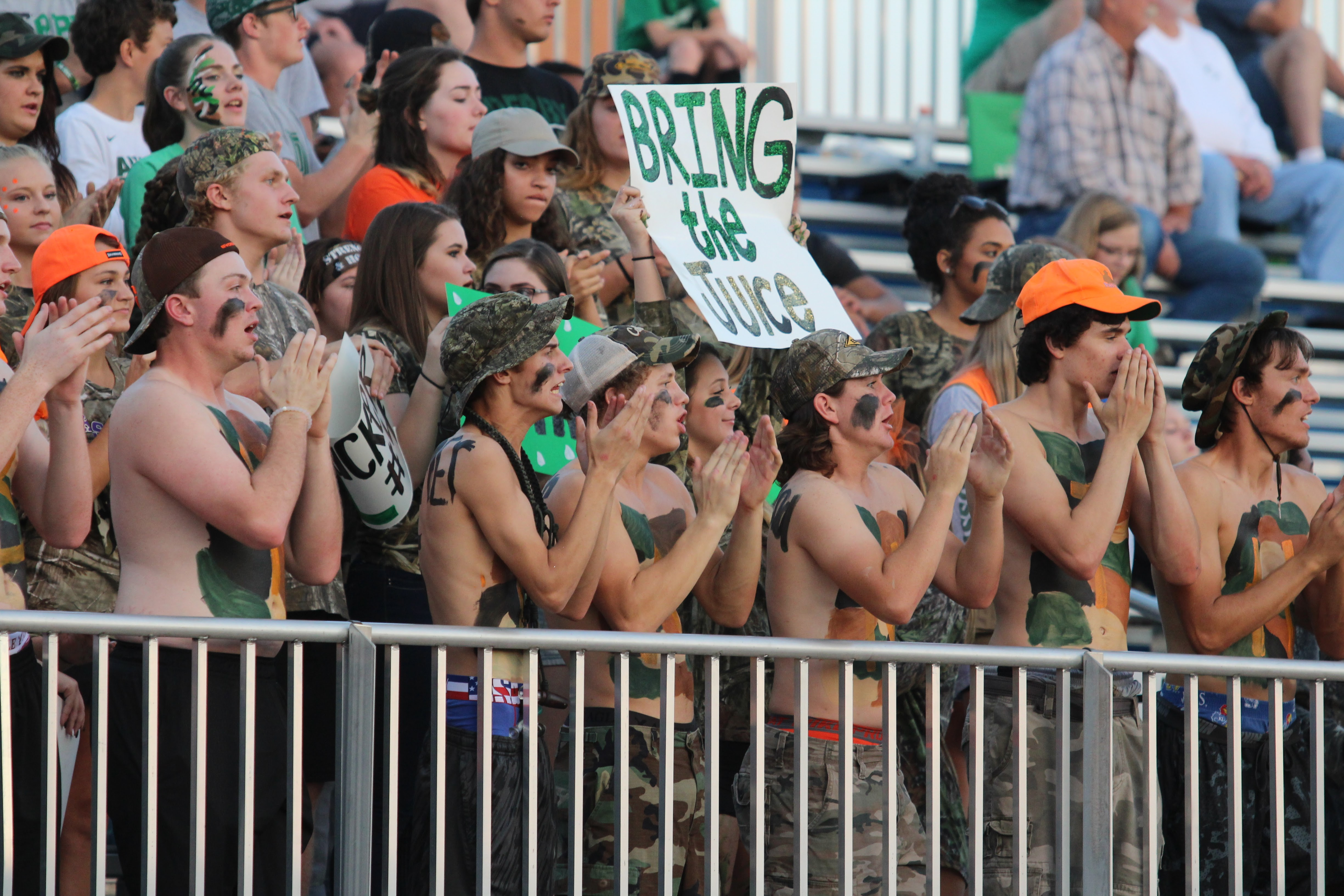 "Derby students cheers from the stands with a sign that read ""Bring the Juice"""